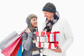 Mature couple in winter clothes holding gifts — Stock Photo