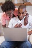 Couple together on the couch using laptop — Stock Photo