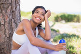 Fit woman sitting against tree holding water bottle — Stock Photo