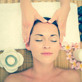 Smiling brunette enjoying a head massage — Stock Photo