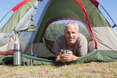 Happy camper smiling at camera lying in his tent — Stock Photo