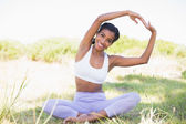 Fit woman sitting on grass in lotus pose smiling at camera — Stock Photo