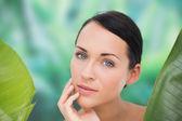 Prachtige naakt brunette poseren met groene bladeren — Stockfoto