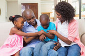 Happy family relaxing on the couch — Stockfoto
