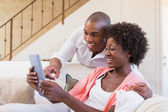 Cute couple relaxing on couch with tablet pc — Stock Photo