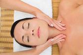 Peaceful brunette enjoying a facial massage — Stock Photo