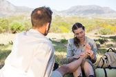 Caring girlfriend giving her boyfriend a foot rub on a hike — Stock Photo