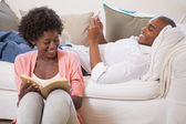 Couple together reading book and using smartphone — Stock Photo