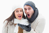 Attractive young couple in warm clothes blowing — Stock Photo
