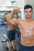 Homem musculoso sem camisa flexionando os músculos em academia — Foto Stock