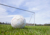 Football on an empty pitch in front of goal — Stock Photo
