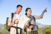 Hiking couple consulting the map in the countryside — Zdjęcie stockowe