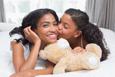 Pretty woman lying on bed with her daughter kissing cheek — Stock Photo