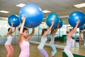 Fitness class holding up exercise balls in studio — ストック写真