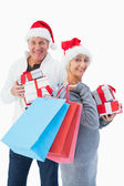 Festive mature couple in winter clothes holding gifts and bags — Stock Photo