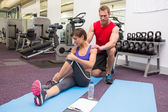 Personal trainer rubbing clients shoulders on mat — Stok fotoğraf