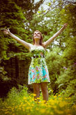 Woman with arms outstretched in field against trees — Stok fotoğraf