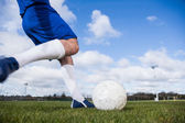 Football player in blue about to kick ball — Stock Photo