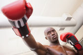 Male boxer attacking with his right in health club — Stock Photo