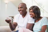 Happy couple watching television on sofa — Stock Photo