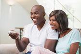 Šťastný pár, dívat se na televizi na pohovce — Stock fotografie