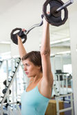 Fit brunette lifting heavy barbell over head — Stock Photo
