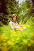 Thoughtful woman relaxing in field — Stock Photo
