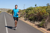 Athletic man jogging on open road — Stock Photo