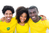Happy brazilian football fans in yellow sitting on couch  — Stock Photo