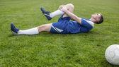 Football player in blue lying injured on the pitch — Stock Photo