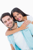 Happy casual man giving pretty girlfriend piggy back — Stock Photo