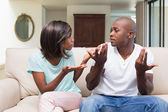 Unhappy couple having an argument on the couch — Stock Photo