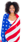 Pretty girl wrapped in american flag smiling at camera — Photo