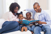 Happy family on the couch reading storybook — Stock Photo