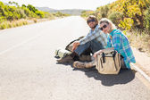 Couple sitting on road waiting for lift — Stock fotografie