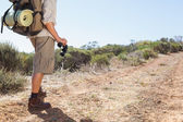 Hiker holding his binoculars on country trail — Stock Photo