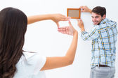 Happy young couple putting up picture frame — ストック写真