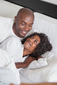 Happy couple cuddling together in bed — Stock Photo