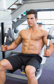 Muscular man working on abdominal machine at the gym — Stock Photo