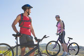 Fit cyclist couple standing at the summit smiling at each other — Stock Photo