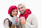 Attractive young couple in warm clothes holding mugs — 图库照片