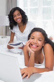 Mother reading magazine with daughter using laptop on bed — Stock Photo