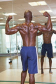 Rear view of muscular man flexing muscles in gym — Stock Photo