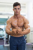 Shirtless muscular man flexing muscles in gym — ストック写真