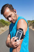 Athletic man changing the music on a run — Stock Photo