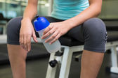 Fit woman sitting on bench holding sports bottle — Foto Stock
