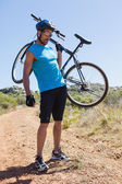 Fit cyclist carrying his bike out in the countryside — Stock Photo