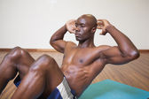 Muscular man doing abdominal crunches in gym — Stock Photo
