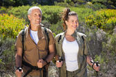 Hiking couple standing with walking poles — Stock Photo