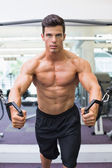 Shirtless muscular man using resistance band in gym — Stockfoto
